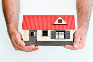 Man hands holds toy house isolated on white background with copy space.Concept photo of real estate business, home Insurance, house rental,buying, renting, mortgage, finance,service and repair costs